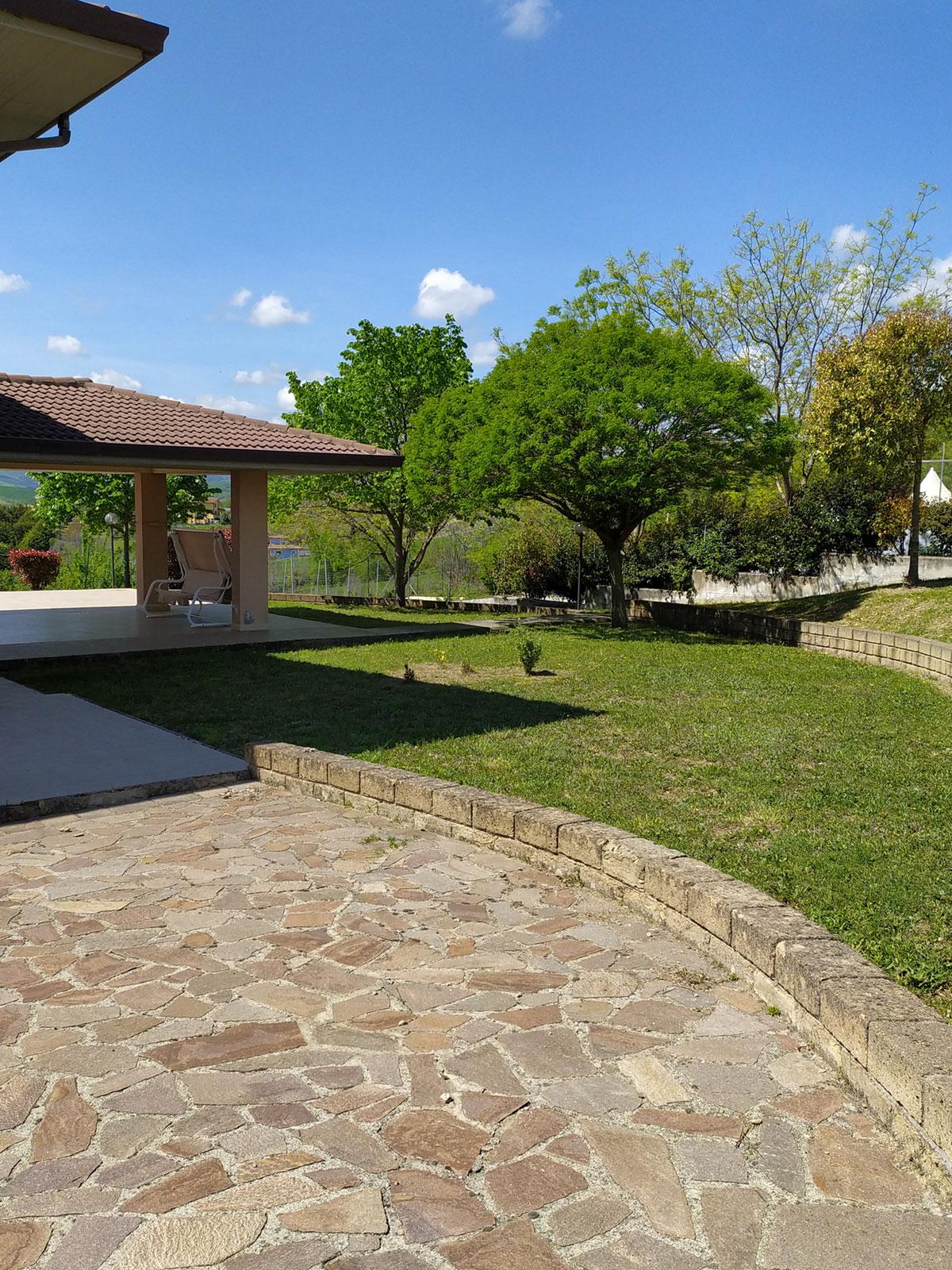 Giardino esterno di un villino con prato e pavimento in pietra