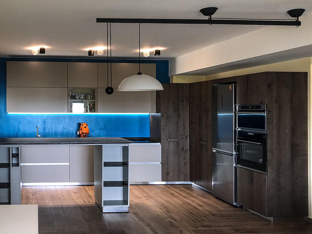 Cucina moderna con parete color blu elettrico e colonna forno classico più microonde