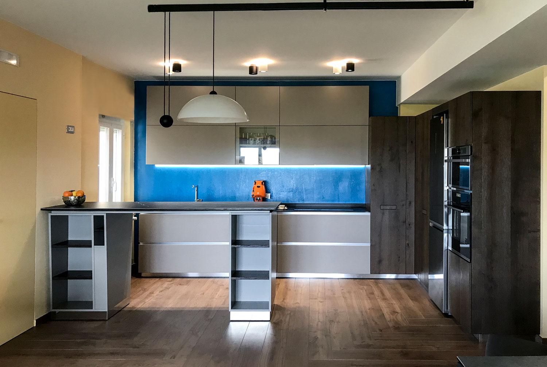 Cucina moderna con parete di color blu elettrico, scaffalatura ed elettrodomestici